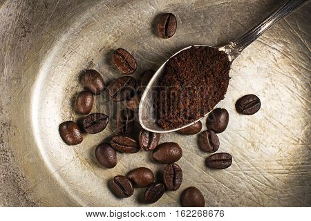Fresh ground Coffee in spoon on plate close up.