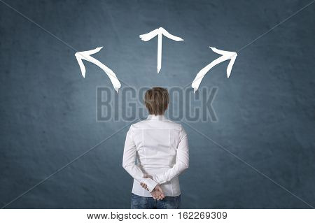 Making decisions for the future businesswoman standing in front of three direction arrow choices left right or move forward.