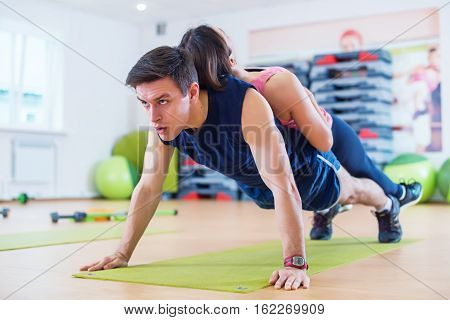 Fit man doing push-ups with woman on back in gym using own weight. Sport training arms, teamwork