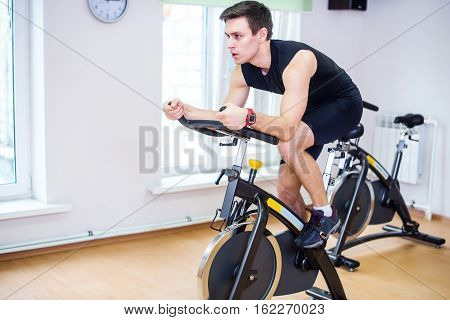 Athlete man biking in the gym, exercising his legs doing cardio training cycling bikes.