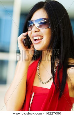 Happy busy young beautiful woman talking on cell phone.