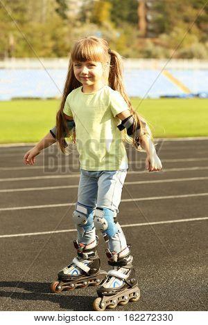 Cute little girl on roller skates on track