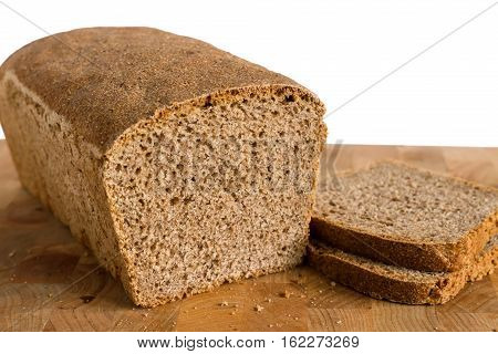 Fresh homemade tin bread with 2 slices on a cutting board