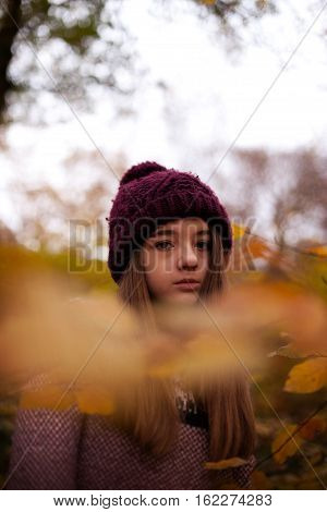 Pretty young girl looking Autumnal through leaves in a forrest