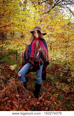 Young teenage girl standing in a forrest in Autumn surrounded by pretty Autumnal colours
