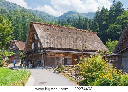 OGIMACI JAPAN - AUGUST 01 2016: Furosato Guesthouse hosted in old house of unique gassho style with thatched roof in Ogimachi village of Shirakawa-go district. World Heritage Site of UNESCO