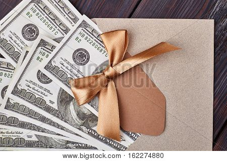 Blank greeting card and dollars. Ribbon bow on envelope. Money as modern idol.