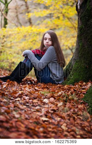Pretty young girl sitting on dried leaves in a forrest in Autumn