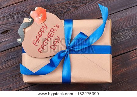 Card and gift for father. Present box on wooden backdrop. Support your dad.