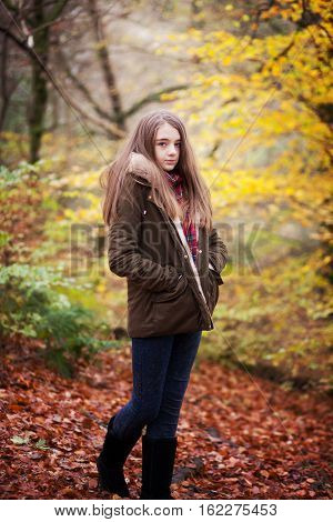Young teenage girl standing with her hands in her coat pockets in a forrest in Autumn