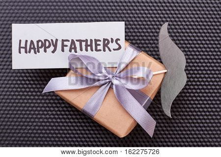 Father's Day card on gift. Mustache, present box, black backdrop. Father will be happy.