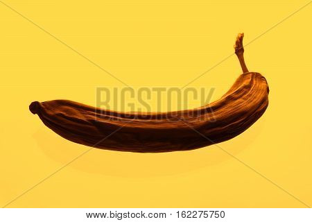 Creative photo spoiled banana in a warm yellow filter