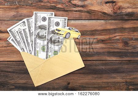 Dollars in envelope and car. Yellow paper car and cash. Spend money wisely.