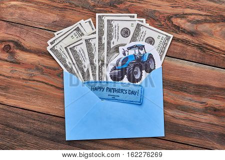 Money on Father's Day. Greeting card and paper tractor. Support dad's dream.