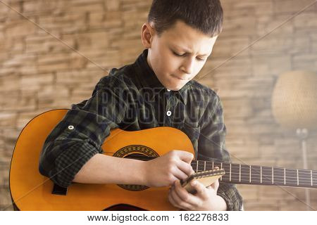 Boy With Acoustic Guitar Writing Songs In Living Room