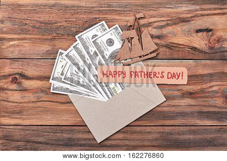 Greeting card, chipboard ship, money. Father's Day card and dollars. Sea voyage as a gift.