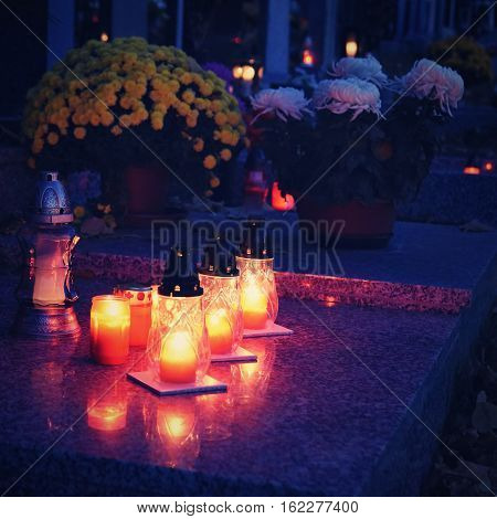 Beautiful autumn concept. Cemetery and Halloween. Candle in a lantern on the grave. Background for Halloween.