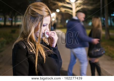 Young Woman Crying in the Night . Betrayal and Infidelity concept. Couple Breaking Up.