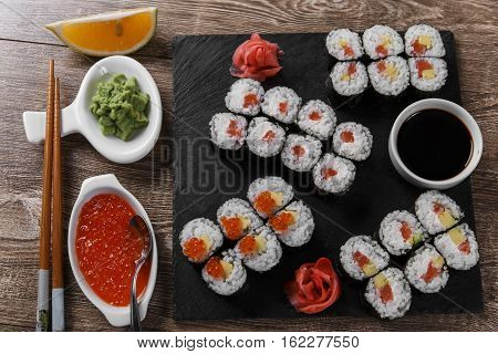 sushi rolls and ingredients served on a wooden surface