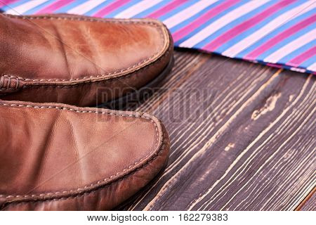 Necktie and brown shoes. Footwear on wooden background. Buy and wear with pleasure.
