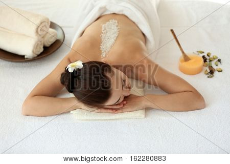 Spa concept. Young woman lying on massage desk with scrub on back