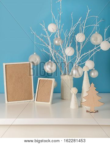 Vase in white knitted cover with white branches and Christmas toys. Empty wooden frame decorated with white yarn. Christmas tree made from white yarn.
