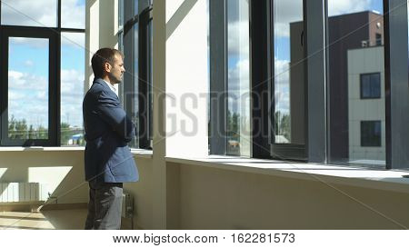 a successful businessman looks out the window and ponders the business plan in modern office