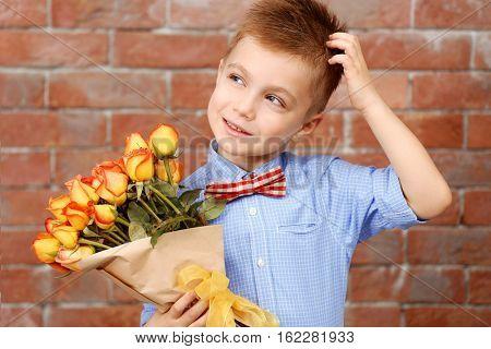 Cute boy with bouquet of beautiful flowers near brick wall