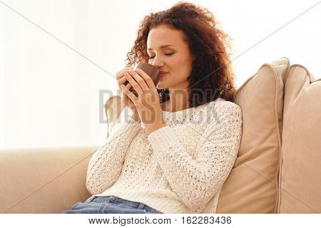 Young beautiful woman holding cup of coffee and sitting on sofa in the room