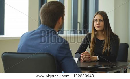 a beautiful woman answers questions of the employer at the interview