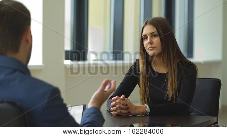 beautiful businesswoman in a black dress answering questions of the employer in modern office
