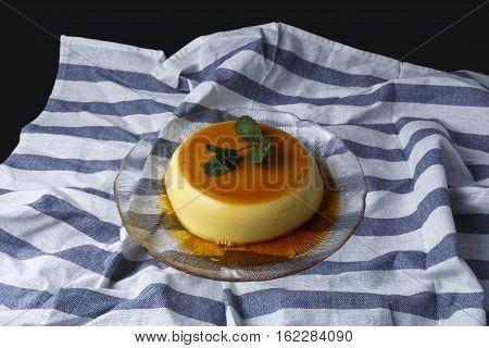 Vanilla flan served in glass dish on a kitchen cloth with black background