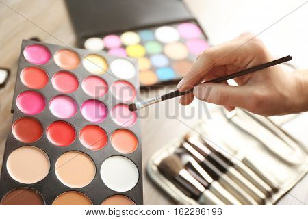 Female hand with palette of lipsticks and tonal foundation, closeup