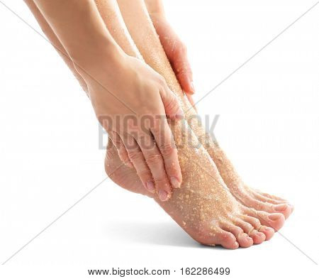 Woman massaging feet with scrub on white background