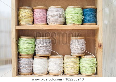 Color thread for sewing on spools on a wooden background