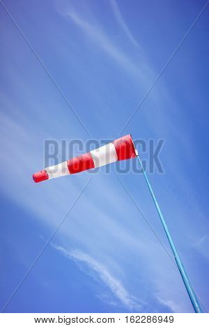 Red And White Windsock Blows Against A Blue Sky.