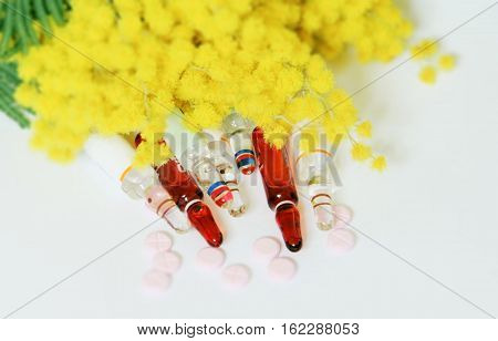 Medical ampules and tablets with soft background mimosa,with space for writing