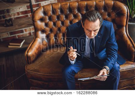 Stubbornly composing mature man is sitting on couch. He holding tablet of documents