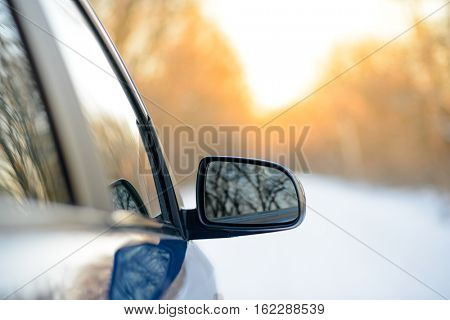 Close up Image of Side Rear-view Mirror on a Blue Car in the Winter Landscape with Evening Sun