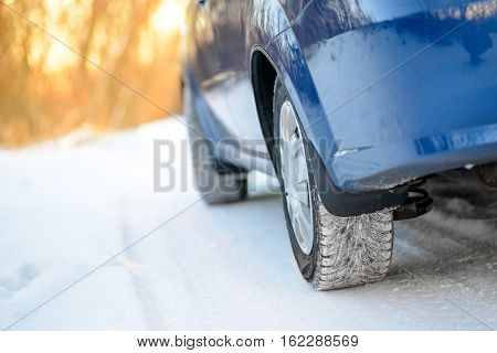 Close-up Image of Winter Car Wheel on the Snowy Road. Drive Safe Concept.