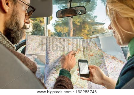 hipster couple lost on road trip in car looking for destination on the map and on gps app on smartphone