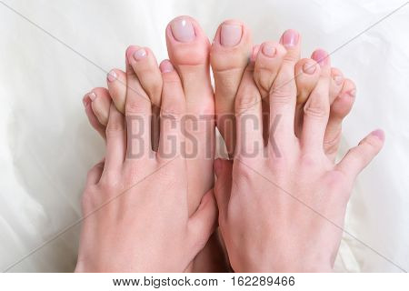 Female fingers between toes on white background. Beautiful hands and feet with nude nail manicure and pedicure