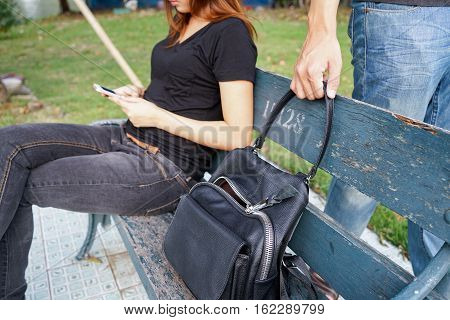 Thief trying to steal and walk away the shoulder bag while woman using mobile phone and sitting on sofa.