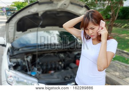 Closeup portrait Stressed woman calling for help on cell phone with mobile phone on road - car breakdown