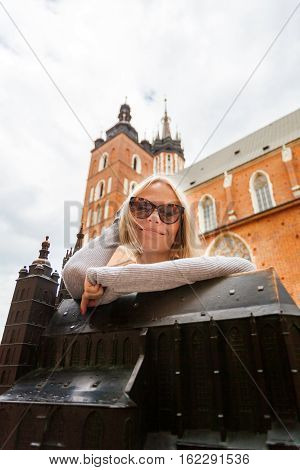 KRAKOW, POLAND - JULY 14, 2016: Female tourist stands on a background of the church of St. Mary in Krakow with a miniature replica of the church in the foreground. Basilica Mariacka. Krakow. Poland.