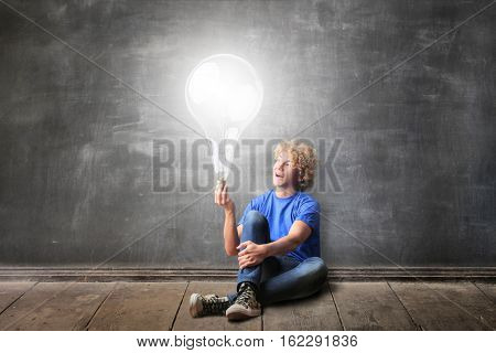Blond guy having a light buld in the hand while sitting on the ground