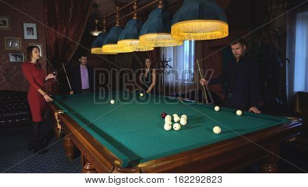 a group of friends playing Billiards, girls watching men playing Billiards