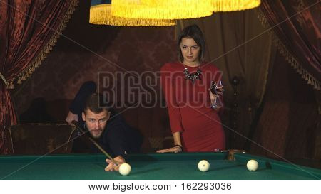 Beautiful happy couple playing billiards, beautiful woman in a red dress watching the game men in Billiards