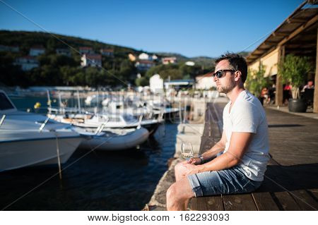 Handsome young man enjoying time at seaside, sitting on wooden pier, holding glass of white wine.