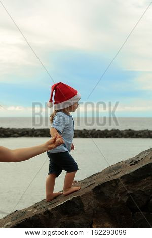 small santa claus cute boy or child in red new year hat going up at beach stony parapet outdoor on water and blue sky natural background celebrates christmas or xmas holidays